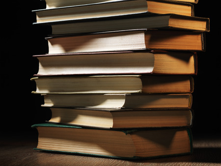 stacked books: Pile of hardcover books stacked on top of one another in a shadowy room on a wooden desk with copyspace in the foreground Stock Photo