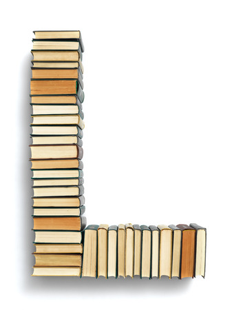 book spines: Letter L formed from the page ends of closed vintage hardcover books standing on a white background Stock Photo
