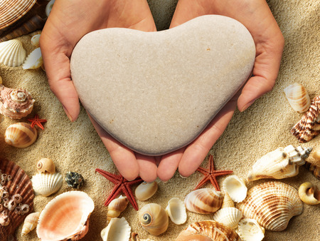 hands cupped: Female hands holding a natural heart-shaped stone in cupped palms over a background of shells Stock Photo