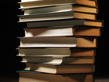 shadowy: Pile of hardcover books stacked on top of one another in a shadowy room  Stock Photo