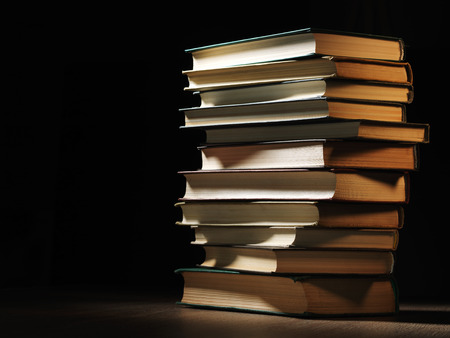 shadowy: Pile of hardcover books stacked on top of one another in a shadowy room on a wooden desk   Stock Photo