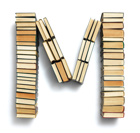 spines: Letter M formed from the page ends of closed vintage hardcover books standing on a white background