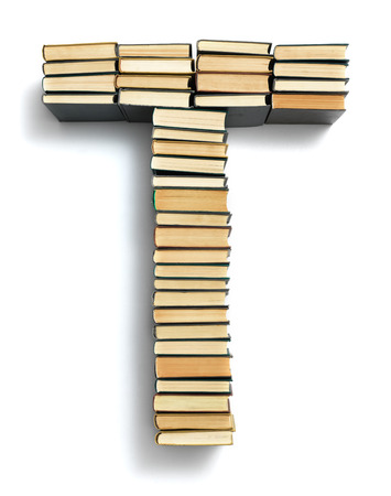 spines: Letter T formed from the page ends of closed vintage hardcover books standing on a white background  Stock Photo