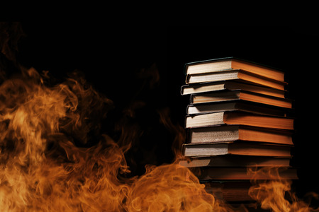 tomes: Conceptual image of a tall stack of hardcover books in a burning fire with flames and smoke swirling around them in a darkened room with copyspace