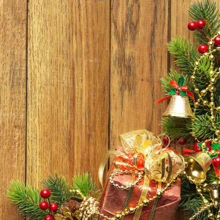 seasonal greeting: Decorated Christmas tree border on wood paneling with gold baubles and bells, a decorative Xmas gift wrapped in a golden bow, holly and beads with copyspace for your seasonal greeting