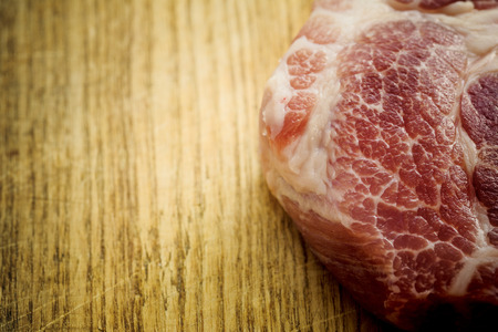 meat counter: Piece of uncooked marbled steak or meat lying on a wooden counter in a kitchen or butchery, overhead view with copyspace
