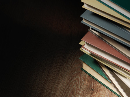 published: Pile of hardcover books stacked on top of one another in a shadowy room on a wooden desk with copyspace in the foreground Stock Photo