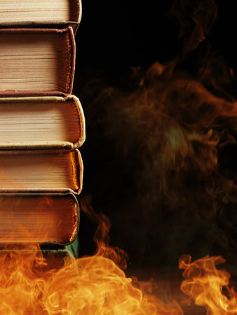 evocative: Pile of hardcover books surrounded with swirling tendrils smoke or vapor in a darkened vintage style room conceptual of magic, fire, spirituality or alchemy
