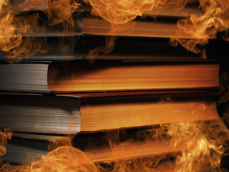tomes: Pile of hardcover books surrounded with swirling tendrils smoke or vapor in a darkened vintage style room conceptual of magic, fire, spirituality or alchemy