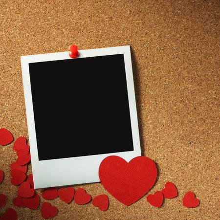 corkboard: polaroid style photo frames on corkboard with paper heart