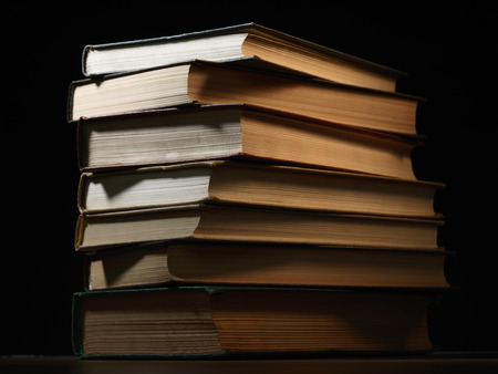 shadowy: Pile of hardcover books stacked on top of one another in a shadowy room on a wooden desk with copyspace in the foreground Stock Photo