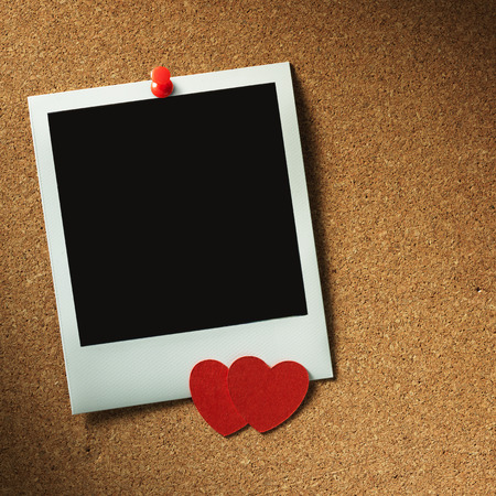 polaroid style photo frames on corkboard with paper heart photo