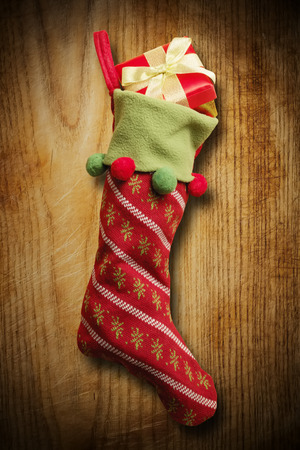 Christmas sock with red gift box on wooden background photo