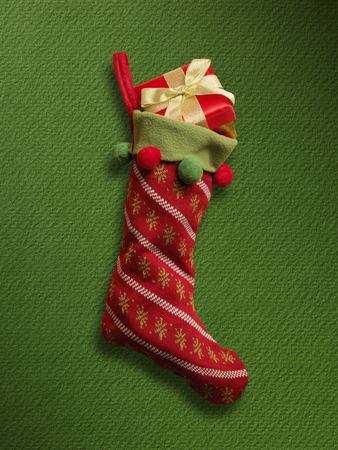 christmas sock: Christmas sock with red gift box on green paper background Stock Photo