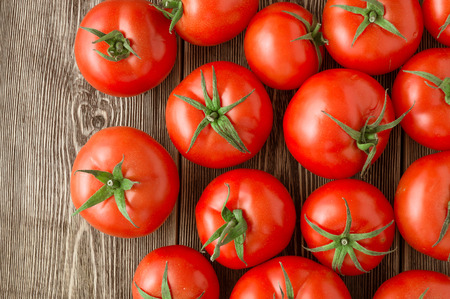Close-up of fresh, ripe tomatoes on wood background Stock Photo