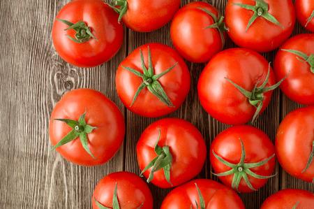 ensalada de tomate: Primer plano de tomates frescos, maduros en el fondo de madera