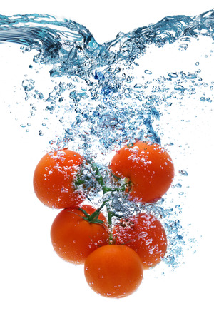 dropped: Fresh tomato dropped into water with splash isolated on white Stock Photo