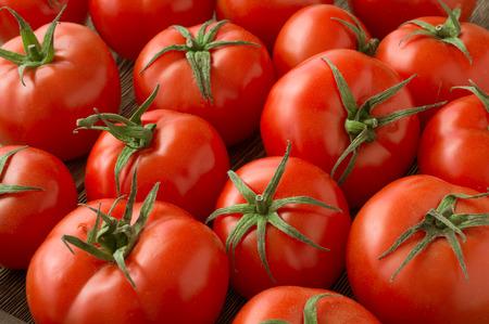 ensalada tomate: tomates fondo rojo. Grupo de tomates Foto de archivo