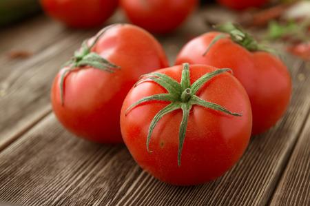 tomates: Primer plano de tomates frescos, maduros en el fondo de madera