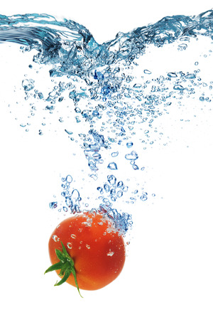 dropped: Fresh Tomato dropped into water with splash isolated on white
