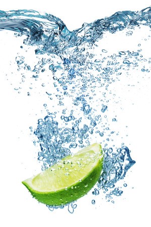 water drip: Fresh lime dropped into water with splash isolated on white