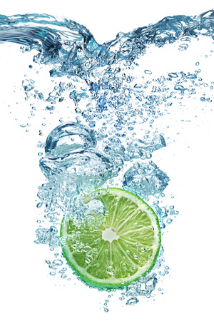 limes: Fresh lime dropped into water with splash isolated on white
