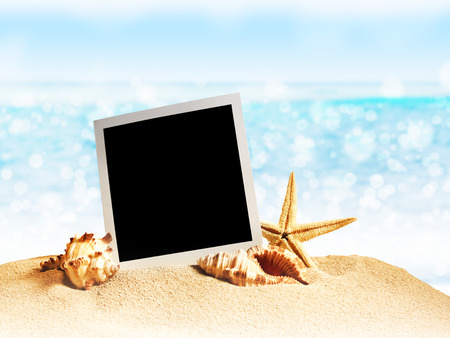 old photo frame: seashells and old photo frame on sand. Close up