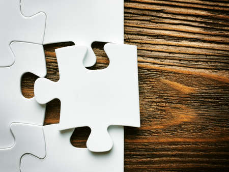 Hand with missing jigsaw puzzle piece. Business concept image for completing the final puzzle piece.wooden background Stock Photo