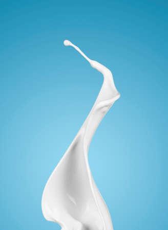 latte fresco: latte o liquido bianco spruzzata su sfondo blu. isolato