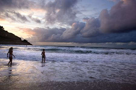 two kids playing on the beach without surveillance at the sunset.  The sky is very nebulous Stock Photo - 988976