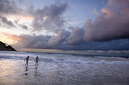 two kids playing on the beach without surveillance at the sunset.  The sky is very nebulous photo