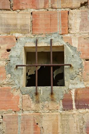rejas de hierro: Ventana vieja en una pared de ladrillo protegido con una rejilla de barras de hierro