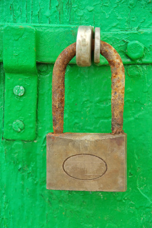Ancient and rusty iron padlock on a wooden green door photo