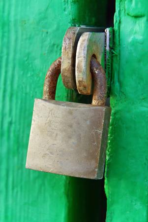 Rusty Padlock on a green wooden door photo
