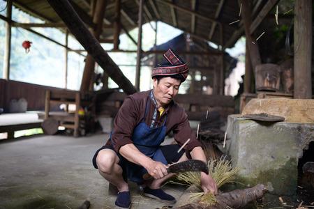 Longsheng County in Guangxi Surabaya Township Square in tangwan crushing, oil master is ready to make tea seed cake straw. Editorial
