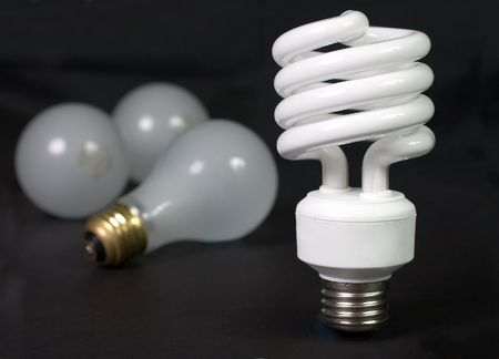 incandescent: Energy saver compact fluorescent light bulb with inefficient incandescent bulbs in the background Stock Photo