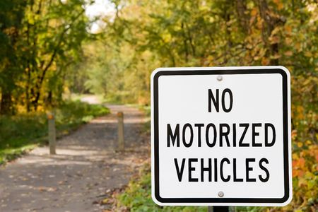 моторизованный: No Motorized Vehicles sign at the head of a bike trail with autumn leaves Фото со стока