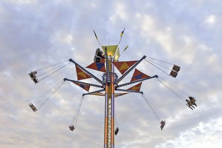 carny: A tower county fair swing ride against a colorful evening sky, the motion creating a slight blur to the passengers