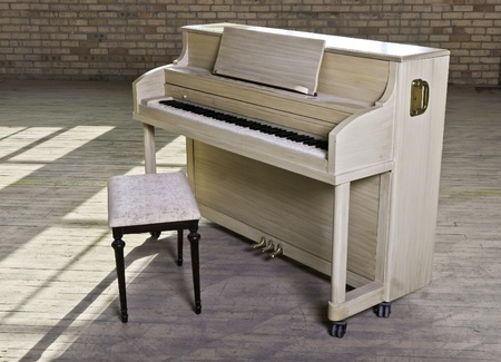upright piano: A blond finished upright piano in an old empty factory