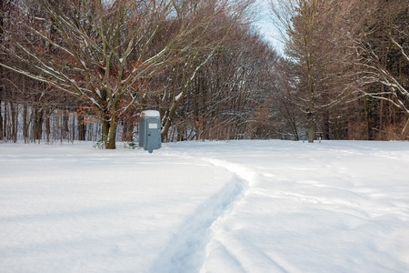 latrine: A curved path in deep snow leads to a portable toilet at the edge of a forest. Stock Photo