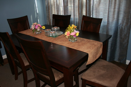 A beautiful hard wood dinning table with fresh flowers.