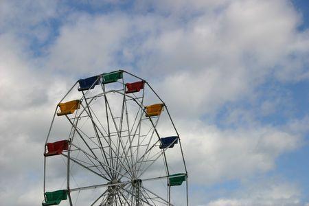 carny: A ferris wheel in a nice blue sky.
