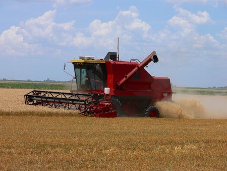 HARVESTER AT WORK IN A WHEAT FIELD Stock Photo
