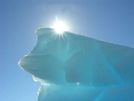 the sun appearing behind a melting iceberg