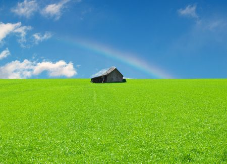 Green field with an old Cabin and Rainbow on blue Sky photo
