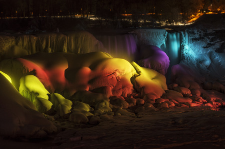 The American Falls with a rainbow of light on them, frozen over in wintertime, Niagara Falls, NY.