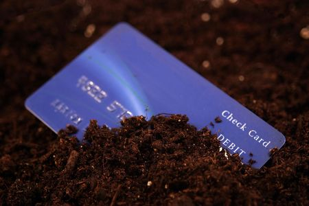 owe: A credit card buried in dirt.. concept buried in debt. Stock Photo