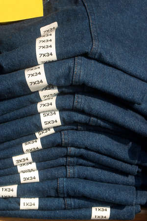 marked: Blue jeans folded neatly with sizes marked. Stock Photo