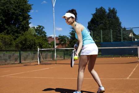 whites: Young woman tennis player on the court  Stock Photo