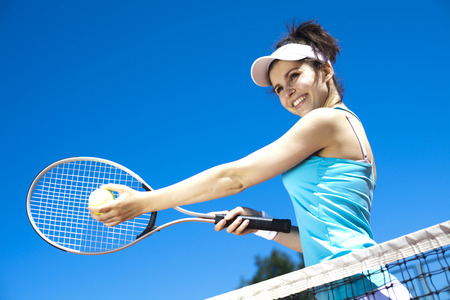 Woman playing tennis in summer photo